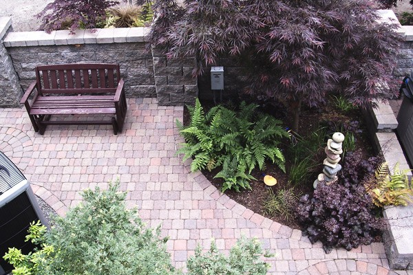 Paver patio, bench and plantings create a quiet space.